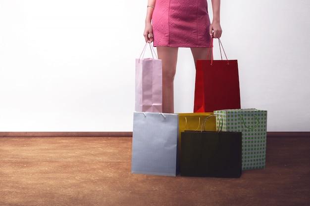 Junge modische frau, die rosa kleid mit einkaufstaschen trägt