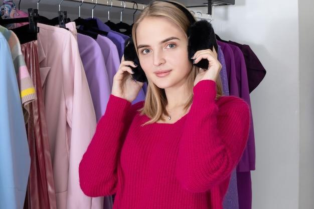 Junge modische frau in einem geschäft, das rosa pullover und flauschige schwarze ohrenschützer trägt.