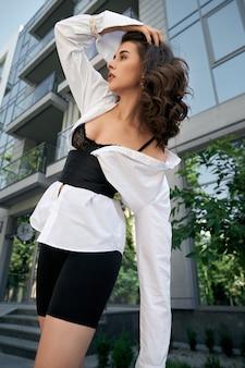 Junge modische geschäftsfrau, die nahe bürogebäude mit großen fenstern auf stadtstraße aufwirft. stilvolles weibliches modell mit weißem hemd auf schwarzem spitzen-bh, breitem korsettgürtel und fahrradshorts im freien.