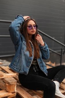 Junge modische hipster-frau in lila trendiger brille in blauer stylischer jeansjacke in schwarzen vintage-jeans, die auf holzpaletten in der stadt posiert. hübsches stilvolles mädchen des mode-modells entspannt sich draußen.