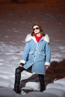 Junge modische vorbildliche frau mit sonnenbrille und mantel auf dem schnee nachts