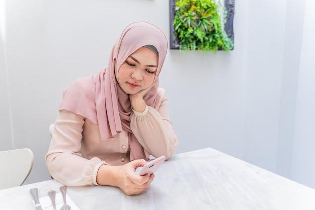 Junge moslemische frau, die auf stuhl im reinraum unter verwendung des mobilen handys schreibt für freund sitzt.