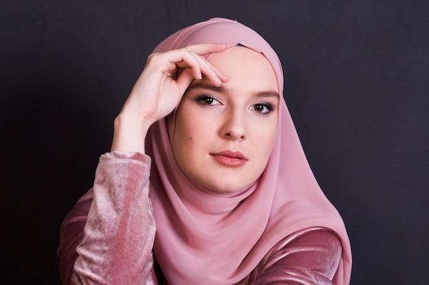 Junge moslemische frau, die hijab vor schwarzer oberfläche trägt