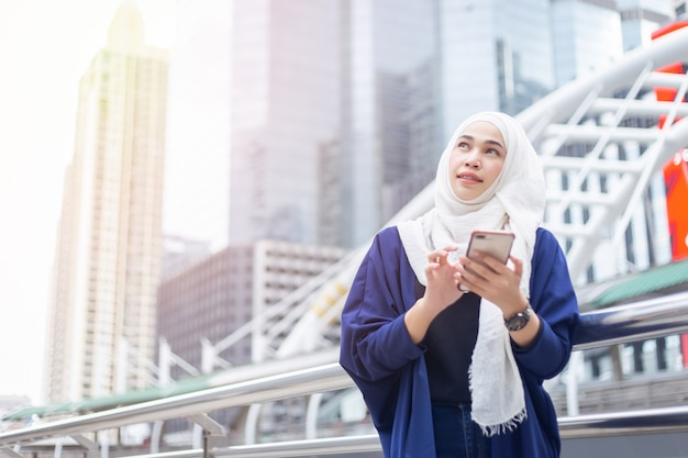 Junge moslemische frau, die smartphone verwendet. blick zum himmel