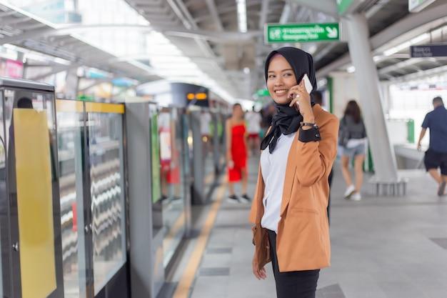 Junge moslemische frau, die telefon auf skytrain station verwendet.