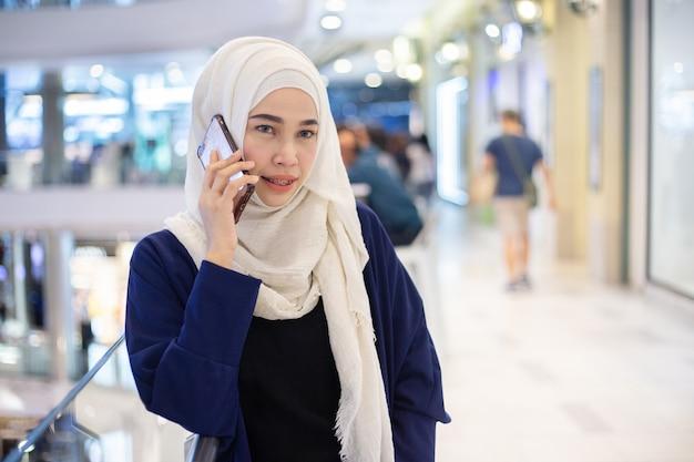 Junge moslemische frau, die telefon im supermarkt verwendet.
