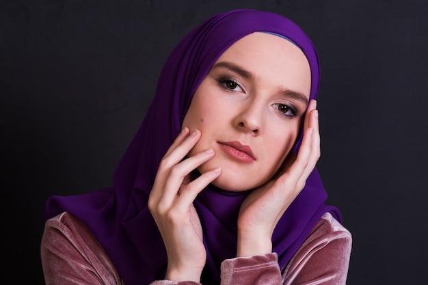 Junge moslemische frau, die tragendes hijab vor schwarzem hintergrund aufwirft