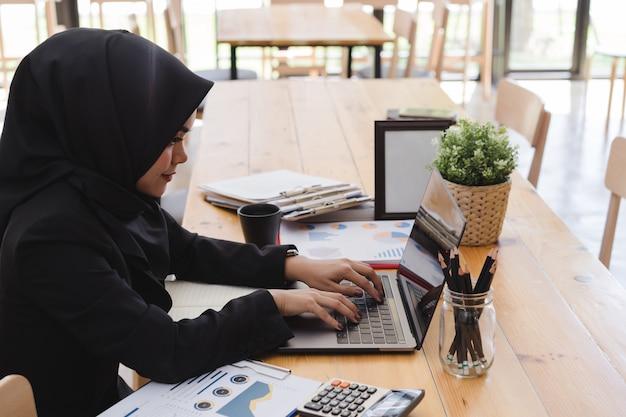 Junge moslemische geschäftsfrau, die das schwarze hijab, arbeitend am coworking trägt.