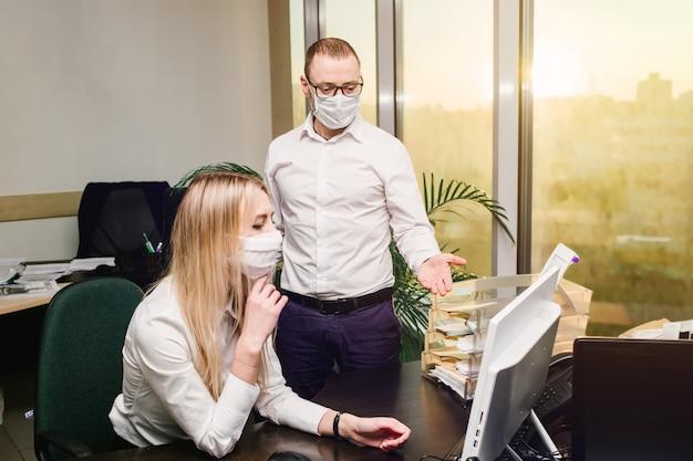 Junge motivierte mitarbeiter in schutzmaske nehmen an online-konferenz teil