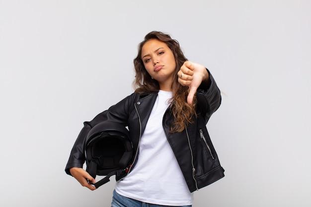 Junge motorradfahrerin, die sich böse, wütend, verärgert, enttäuscht oder unzufrieden fühlt und mit einem ernsten blick die daumen nach unten zeigt