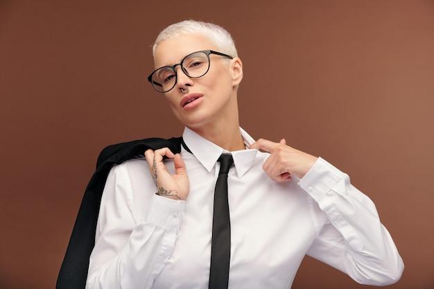 Junge müde blonde geschäftsfrau in formeller kleidung und brille, die den kragen des weißen hemdes verliert und die schwarze jacke an der rechten schulter hält