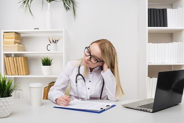 Junge müde erschöpfte frau, die am schreibtisch sitzt und am computer mit medizinischen dokumenten im hellen büro im krankenhaus arbeitet. ärztin im medizinischen kleid schlafen im beratungsraum gesundheitsmedizin-konzept