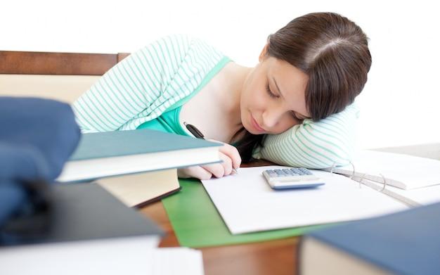 Junge müde frau, die auf einer tabelle studiert