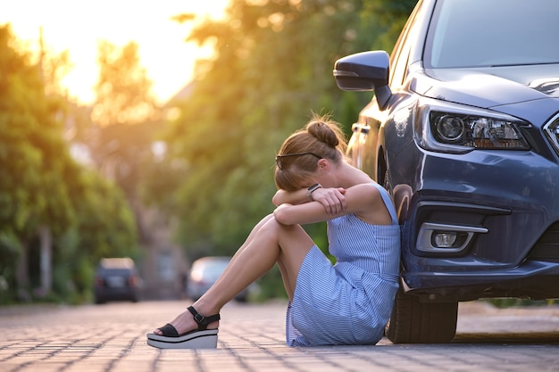 Junge müde frau, die neben dem auto sitzt und auf jemanden wartet. reise- und urlaubskonzept.