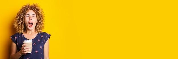Junge müde frau gähnt hält einen pappbecher auf einer gelben oberfläche