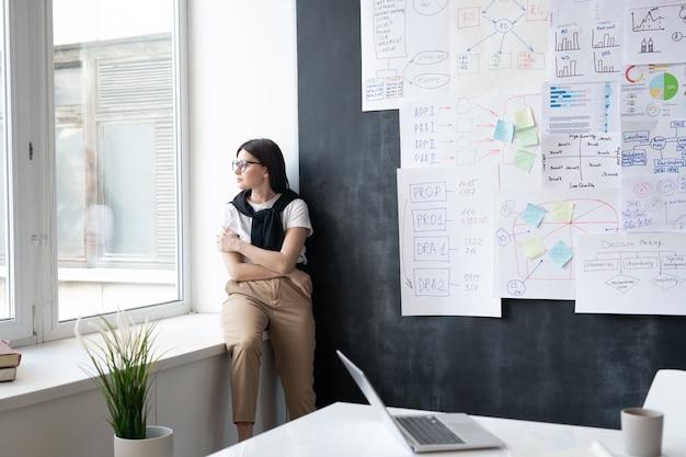 Junge müde geschäftsfrau in der freizeitkleidung, die durch fenster schaut, während auf fensterbank im büro bei pause sitzt
