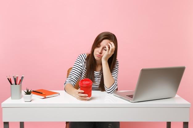 Junge müde schlafende frau lehnt sich an die hand und hält eine tasse kaffee oder tee während der arbeit und sitzt im büro mit pc-laptop einzeln auf pastellrosa hintergrund. erfolgsgeschäftskarrierekonzept. platz kopieren.