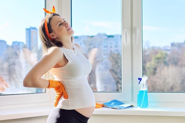 Junge müde schwangere frau in den handschuhen mit lappen- und waschmittelwaschfenster