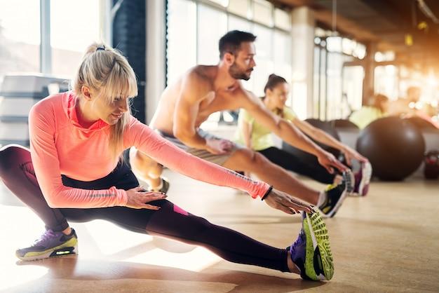 Junge müde sportler in einem fitnessstudio, die nach dem pilates-unterricht ihre beinmuskeln dehnen.