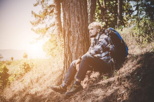 Junge müde wanderer mit rucksack sitzt auf der bergspitze beim ruhe nach dem aktiven spaziergang.