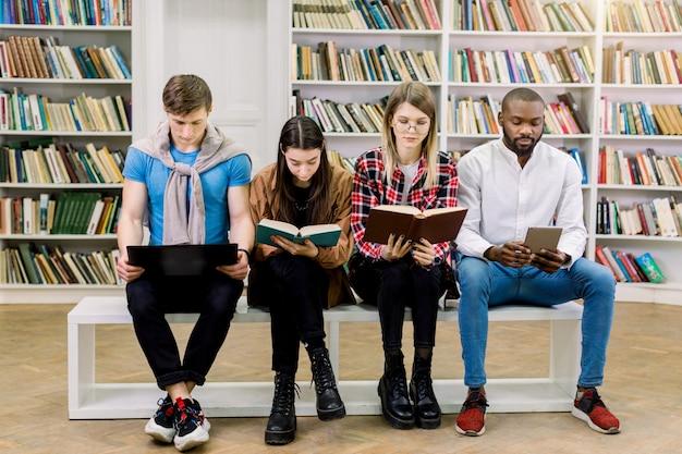 Junge multiethnische kluge studenten, mädchen und jungen, die in der bibliothek aus traditionellen lehrbüchern und e-book und laptop lesen