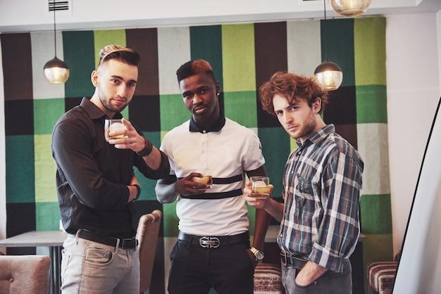Junge multiethnische leute feiern und trinken whisky toast