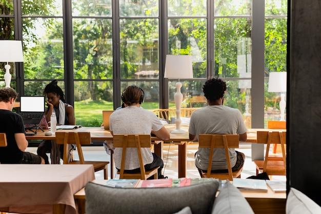 Junge multiethnische touristen, die am laptop im café arbeiten.