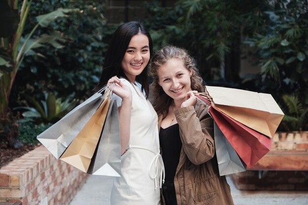 Junge multikulturelle frauen, die einkaufstaschen halten