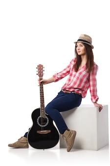Junge musikerin mit gitarre, die auf einem würfel sitzt und sich zurücklehnt. weißer hintergrund.