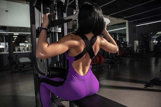 Junge muskulöse frau, die im fitnessstudio mit ausrüstung übt