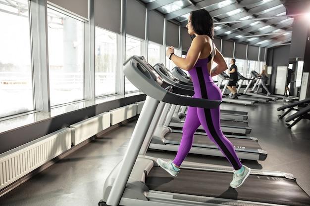 Junge muskulöse frau, die im fitnessstudio mit cardio übt