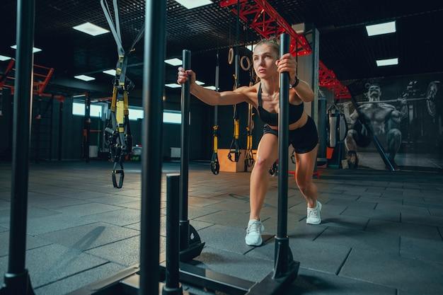 Junge muskulöse frau, die im fitnessstudio übt