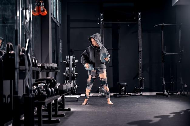 Junge muskulöse kaukasische frau mit kapuzenpulli auf kopf, der boxerhandschuhe hält und im fitnessstudio barfuß steht. nachttrainingskonzept.