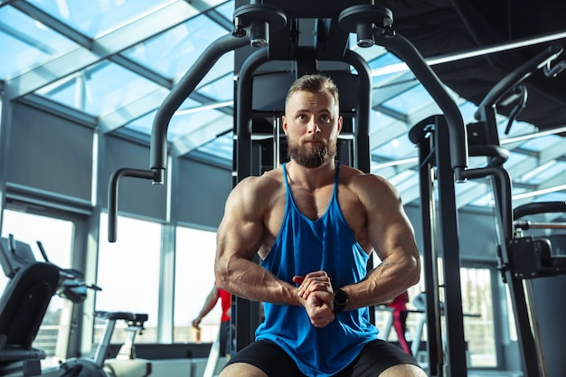 Junge muskulöse sportler, die im fitnessstudio trainieren, kraftübungen machen, üben