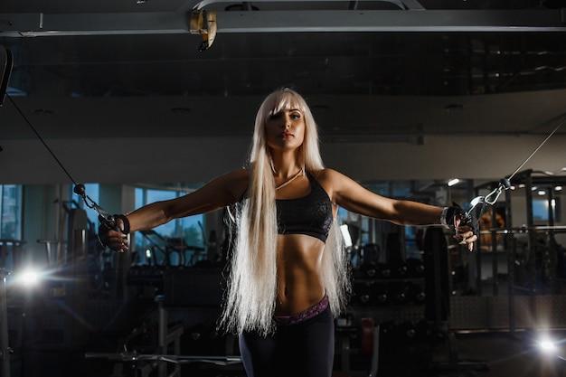 Junge muskulöse sportlerin, die mit blocksimulator im fitnessstudio trainiert und hart für starke armmuskeln arbeitet. mädchen, das vorwärts schaut hände an seiten schiebend.