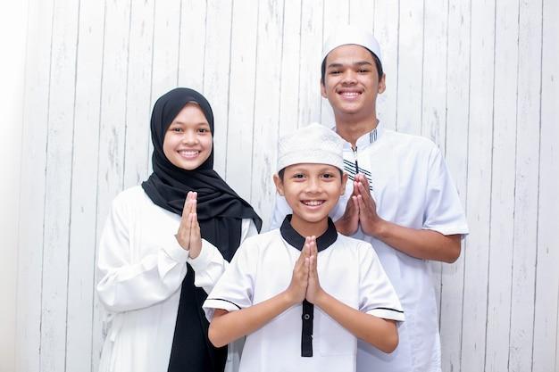 Junge muslimische familie mit handgrußgeste zur vergebung bei eid mubarak-feier