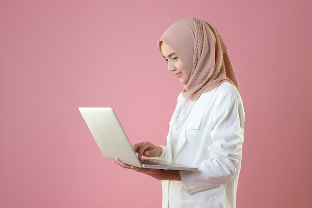 Junge muslimische frau arbeiten online mit dem laptop