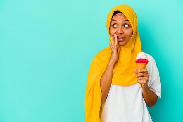 Junge muslimische frau, die ein eis isst, das auf blaue wand isoliert wird, sagt eine geheime heiße bremsnachricht und schaut zur seite