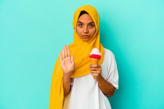 Junge muslimische frau, die ein eis isst, das auf blauem hintergrund lokalisiert wird, der mit ausgestreckter hand steht, die stoppschild zeigt, das sie verhindert.