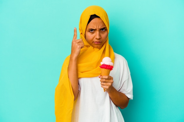 Junge muslimische frau, die ein eis isst, das auf der blauen wand lokalisiert ist, die tempel mit finger zeigt, denkend, konzentriert auf eine aufgabe