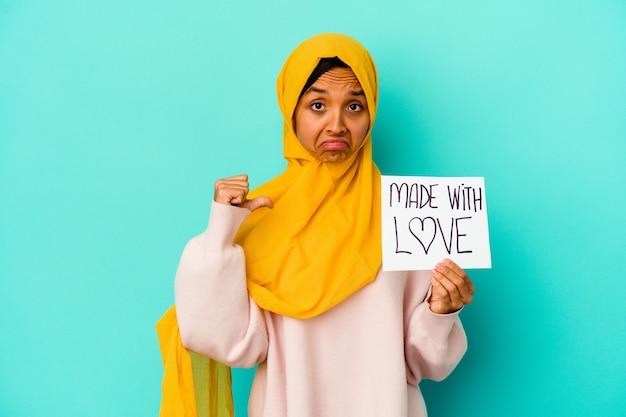 Junge muslimische frau, die ein mit liebe gemachtes plakat hält, das auf blauer wand isoliert ist, fühlt sich stolz und selbstbewusst, beispiel zu folgen