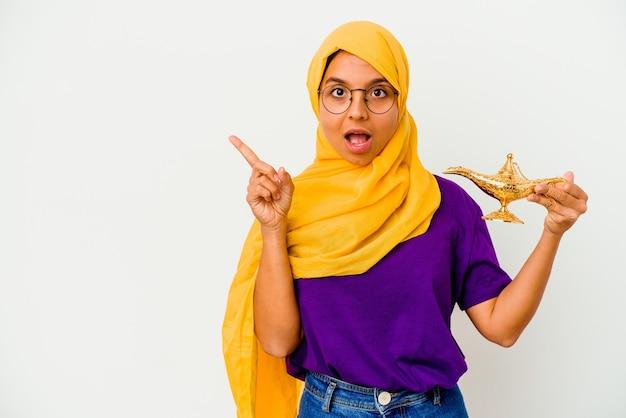 Junge muslimische frau, die eine lampe lokalisiert auf weißer wand hält, die zur seite zeigt