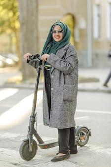Junge muslimische frau, die einen roller auf einer straße fährt
