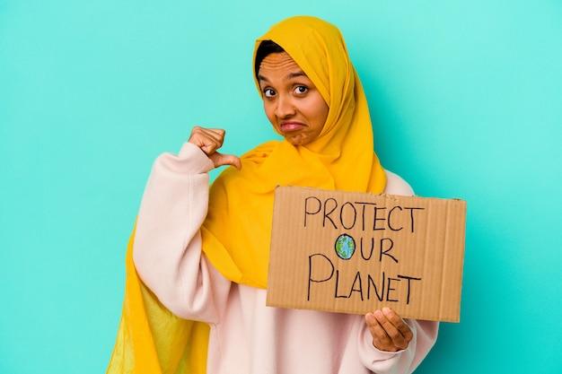 Junge muslimische frau, die einen schutz unseres planeten isoliert auf blauer wand hält, fühlt sich stolz und selbstbewusst, beispiel zu folgen.
