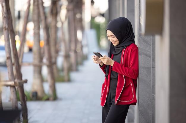 Junge muslimische frau, die erfolg feiert, der handy auf der straße steht