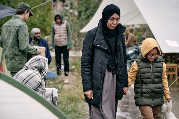 Junge muslimische frau, die ihre tochter mit der hand hält