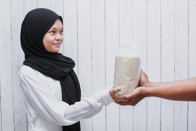 Junge muslimische frau, die im heiligen monat ramadan reis für zakat fitrah als verpflichtung gibt