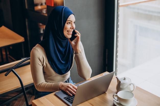 Junge muslimische frau, die in einem café telefoniert und am computer arbeitet?