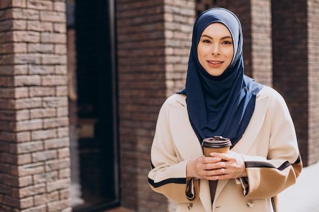 Junge muslimische frau, die kaffee trinkt