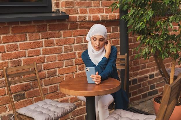 Junge muslimische frau, die über einen videoanruf auf dem smartphone im stadtcafé spricht, arabische frau und technologien